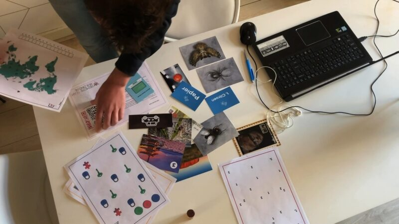 Remote Teambuilding online teambuilding van The Box Company spelattributen op tafel naast laptop