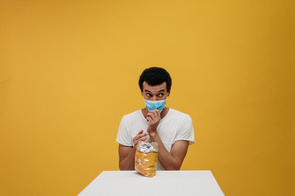Man met mondkapje voor een gele muur met een zak chips