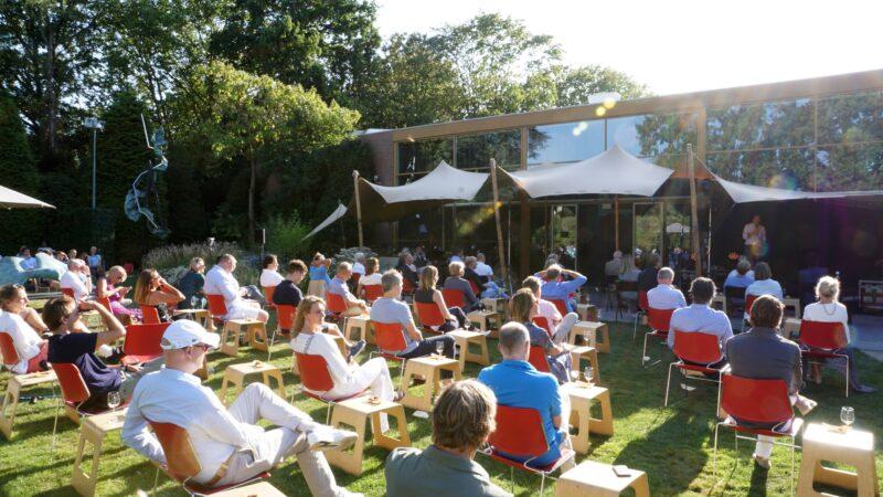 Coronaproof bijeenkomst in de tuin van Singer Laren met rode stoeltjes en een stretchtent