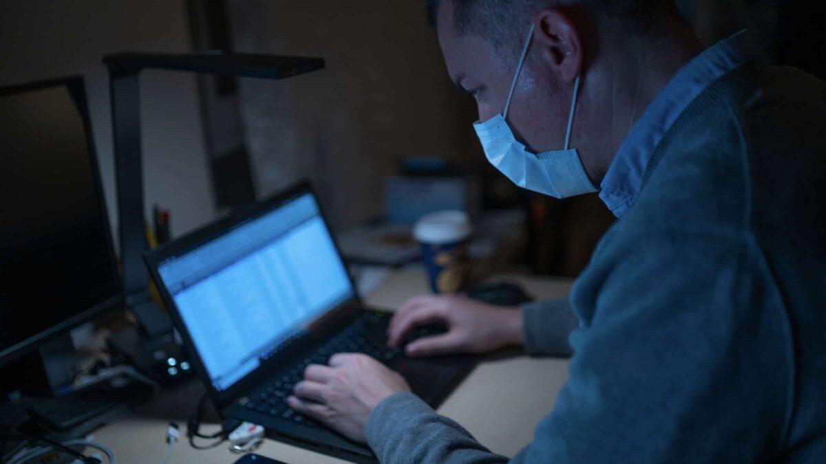 Coronavirus - man met mondkapje -laptop