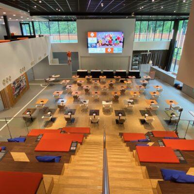 Grote zaal bij KNVB Campus met eenpersoonstafels van bovenaf