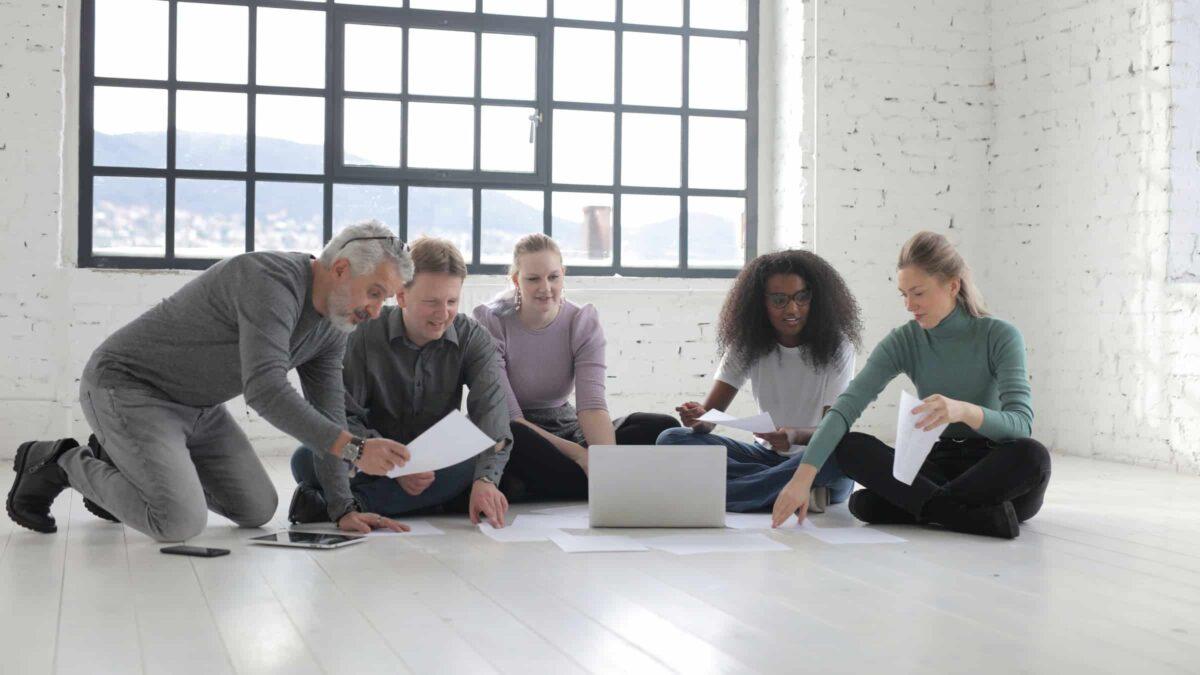 Diversiteit - 5 mensen voor een laptop die zitten op de grond tijdens een brainstorm : vergadering