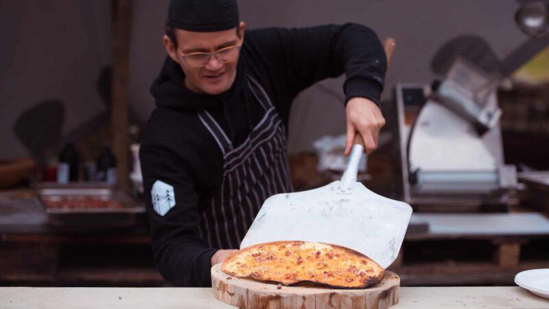Event Inspiration - Kok bij Buiten in de Kuil die een pizza op een houten plank legt