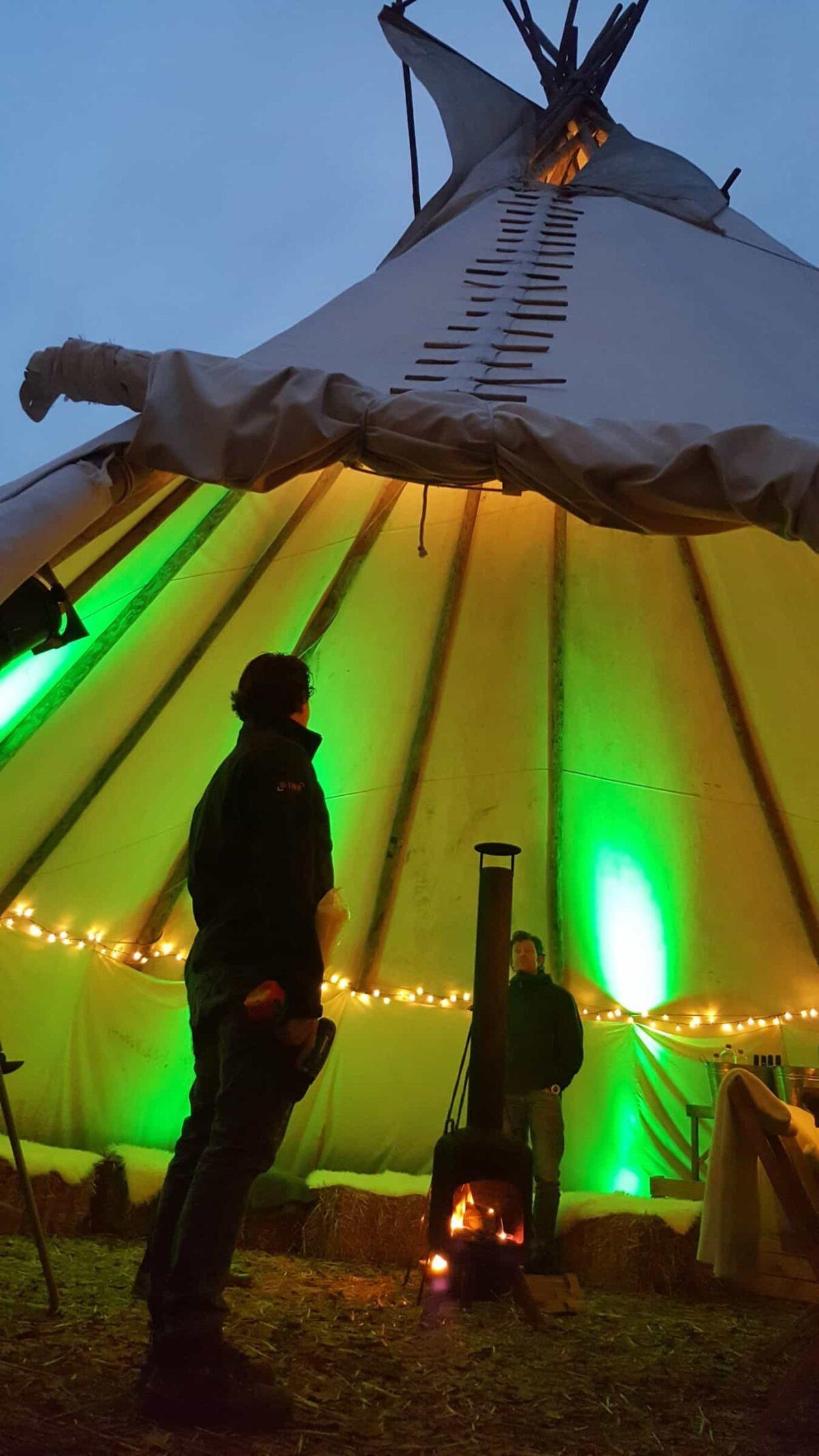 Event Inspiration - Buiten in de kuil verlichte tipitent met mensen bij een heater