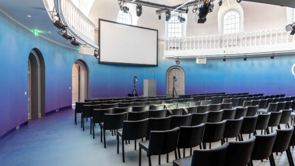Event Inspiration - Coronaproof opstelling voor hybride events in blauwe zaal met balkon bij Amerpodia (foto @LJM_LennertAntonissen) van links gefotografeerd