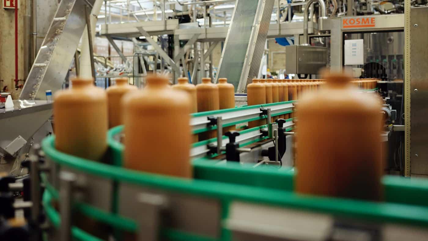 Fabriek met een lopende band waar bruine jeneverflessen op staan