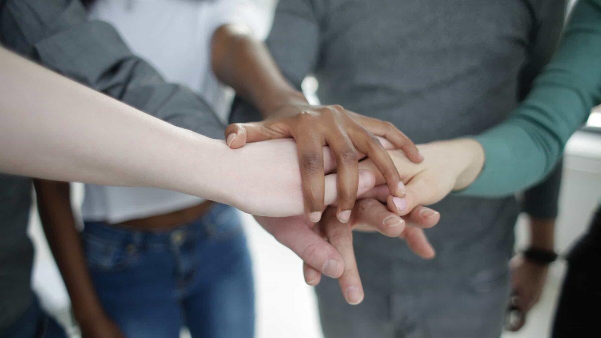 Handen van 4 mensen met verschillende huidskleur