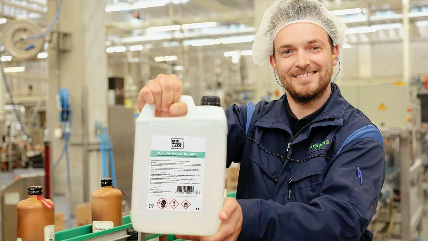 Keep Hands Clean handalcohol jerrycan vastgehouden in een fabriek door een medewerker