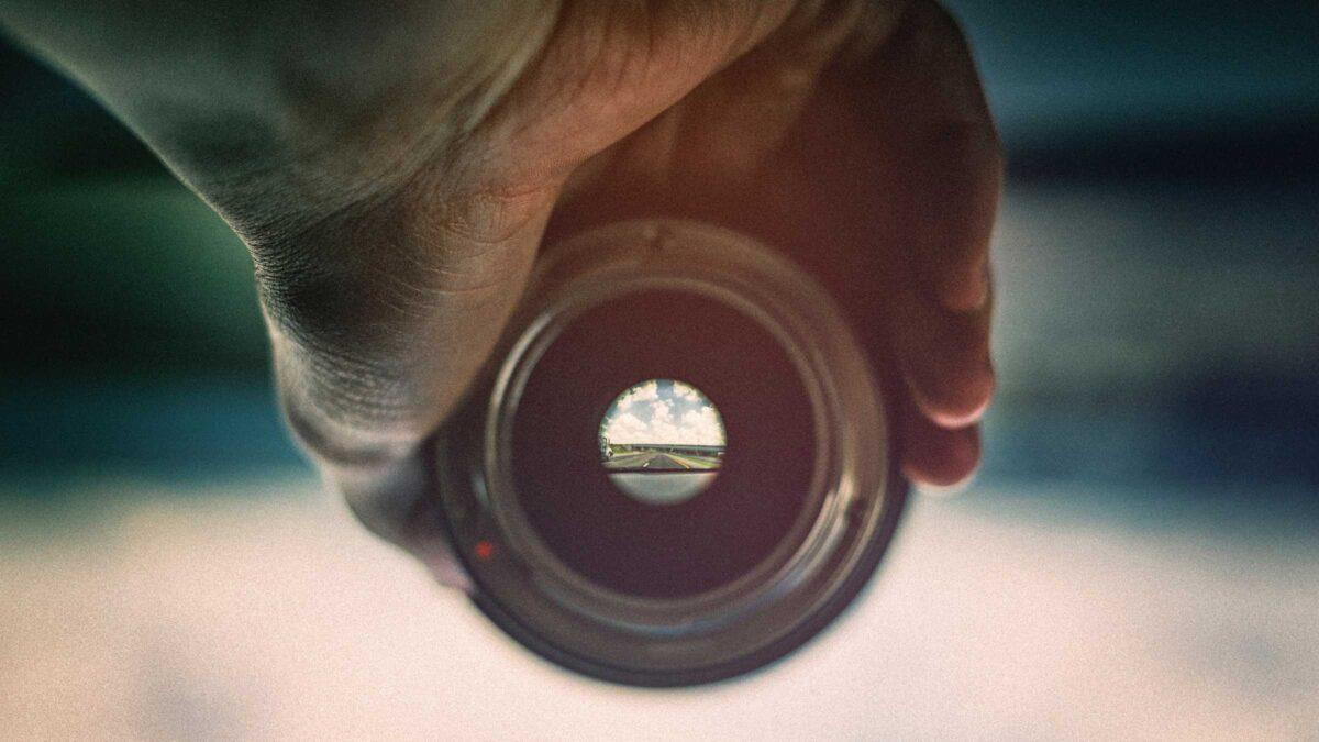 Man houdt lens vast waardoor je ver weg scherp ziet en eromheen vaag - Focus om een goed concept te bedenken