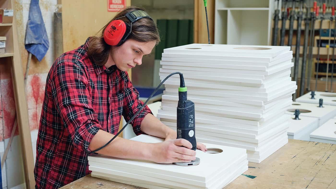 Medewerker van een fabriek die rondjes zaagt uit panelen