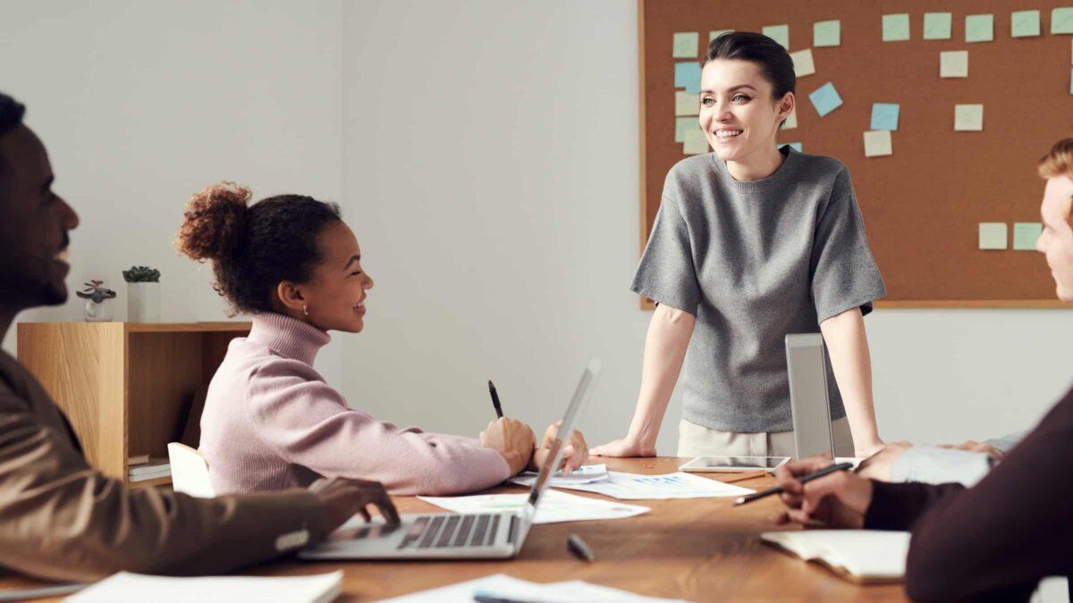 Diversiteit - Vrouw staat aan het hoofd van een tafel tijdens een vergadering en brainstorm waar nog 3 andere mensen bij aanwezig zijn