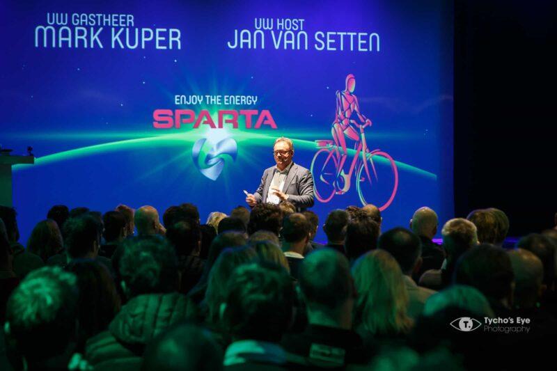 effectgroep-event-sparta-presentatie-fietsen-scherm-met-presentator-en-mensen-in-her-publiek