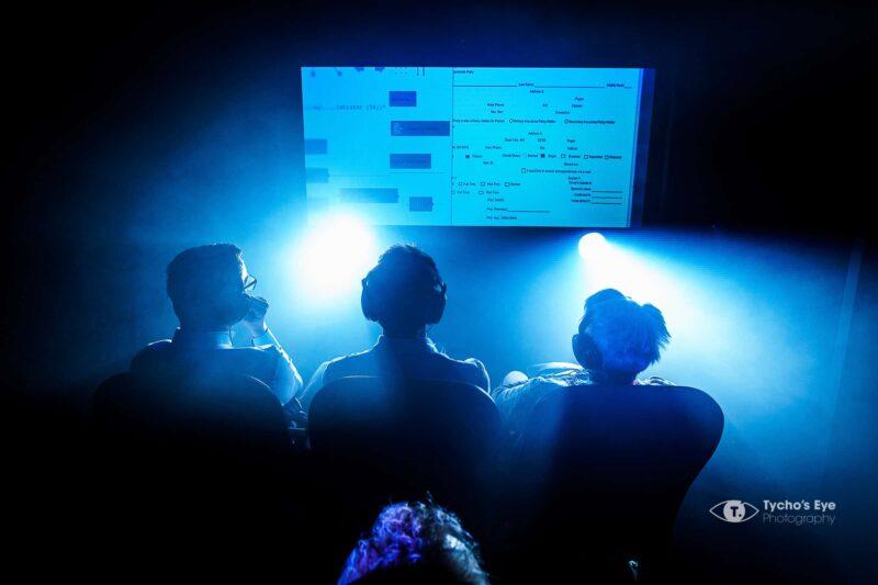 event-bioscoop-donker-blauw licht-presentatie-koptelefoons- mensen