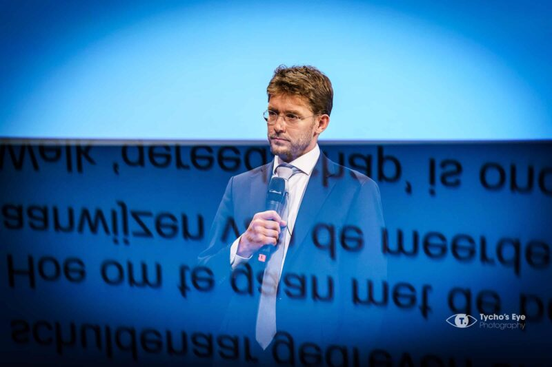 presentator-tijdens-zakelijk-event-met-een-tekst-voor-zich