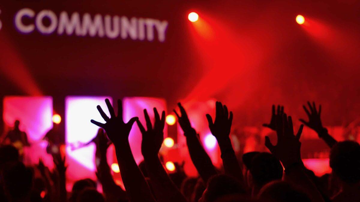 woord community met mensen in een zaal die hun handen omhoog doen