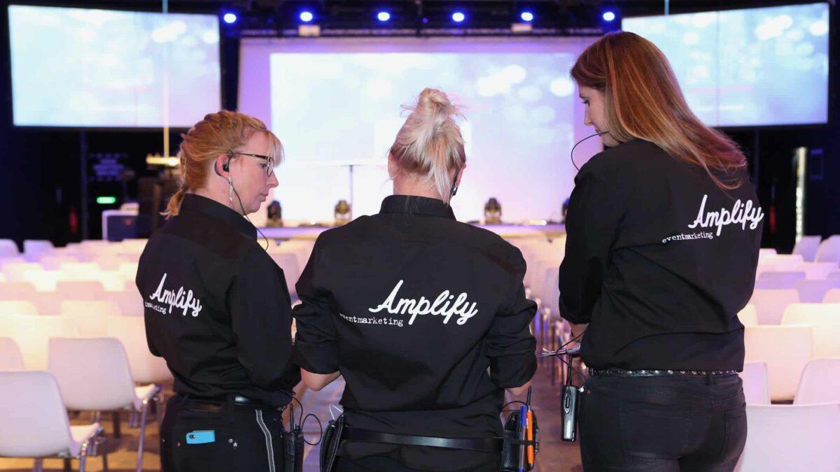 3 hostessen van Amplify EventMarketing tijdens een event in een grote zaal