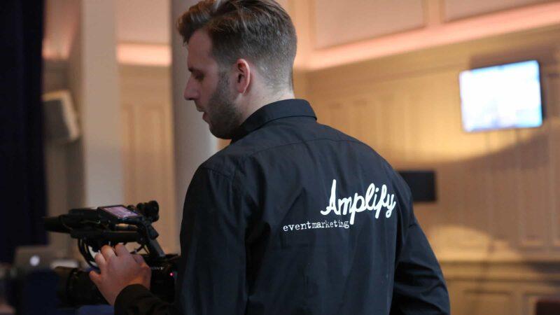 Cameraman op een event met een zwarte blouse met Amplify Eventmarketing erop