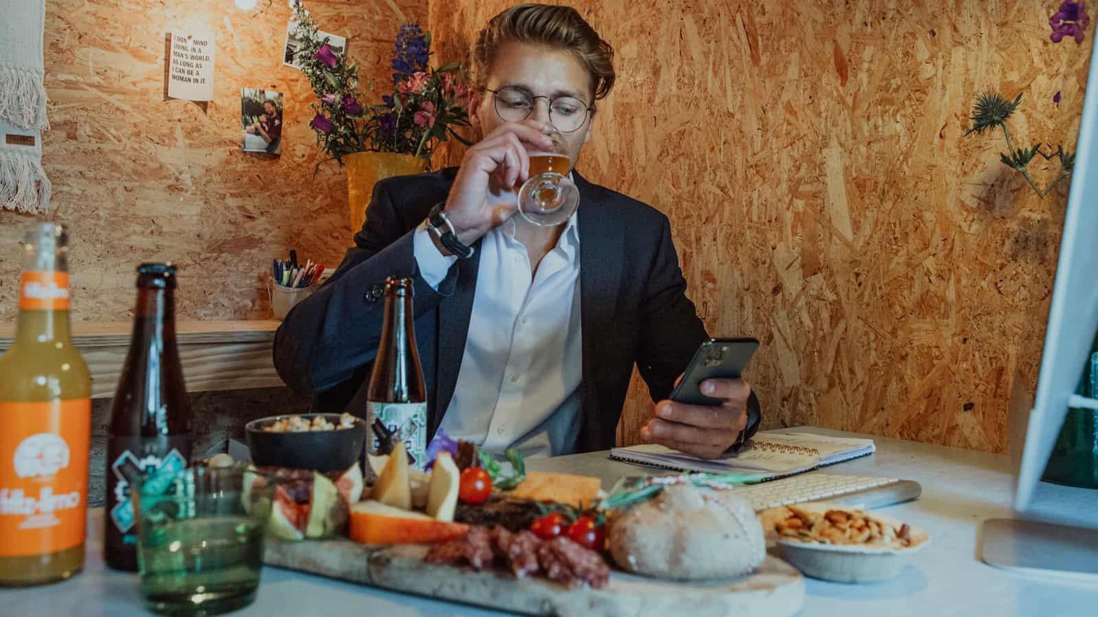 Man die een biertje drinkt tijdens een online meeting met een borrelplank ernaast van Caterbox