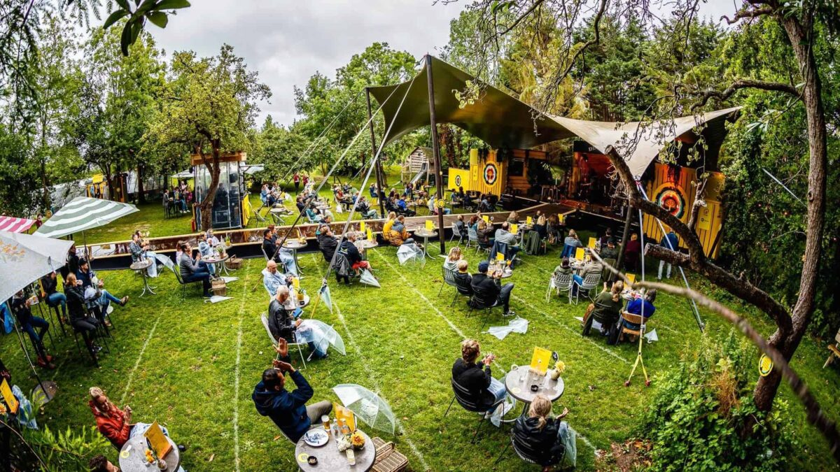 De Brielsche Aap - De Tuin Van 2020 - mensen die op stoelen naar een optreden zitten te kijken in een tuin met eemn stretchtent en podium