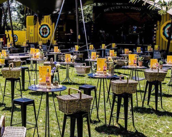 De Brielsche Aap - De Tuin Van 2020 - statafels met krukken en picknickmanden bij een podium