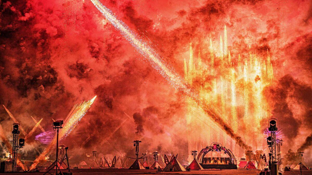 Defqon dj booth met rood en oranje vuurwerk eromheen