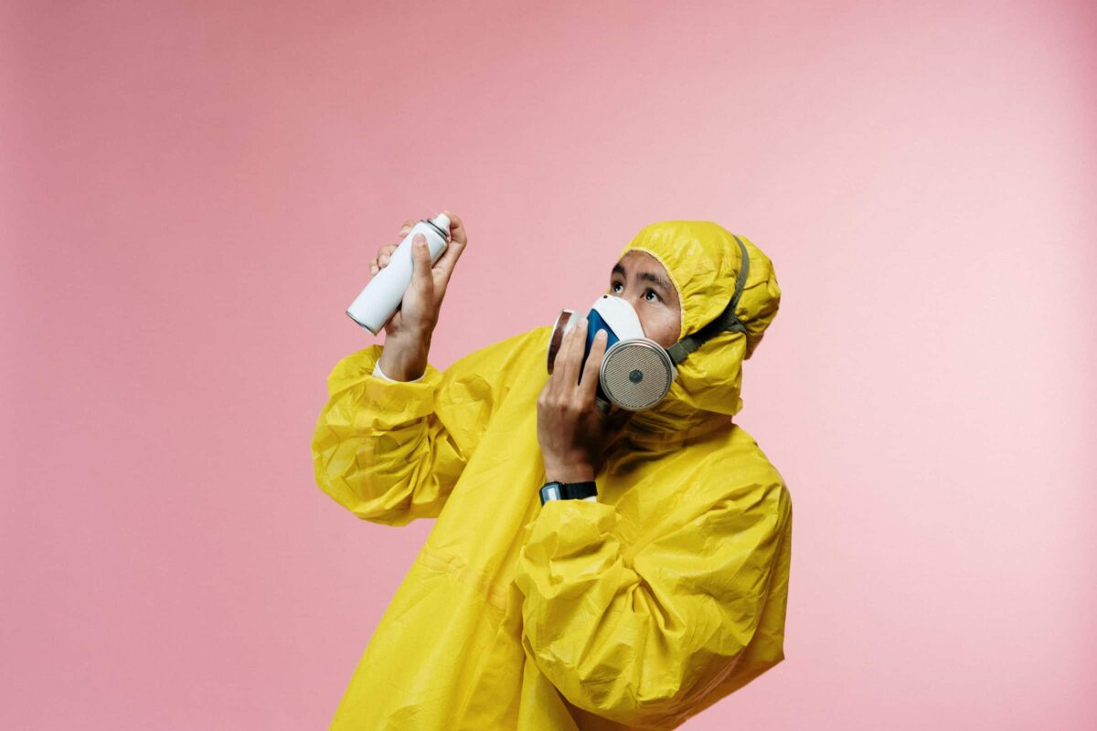 Man in geel pak en masker met spuitbus