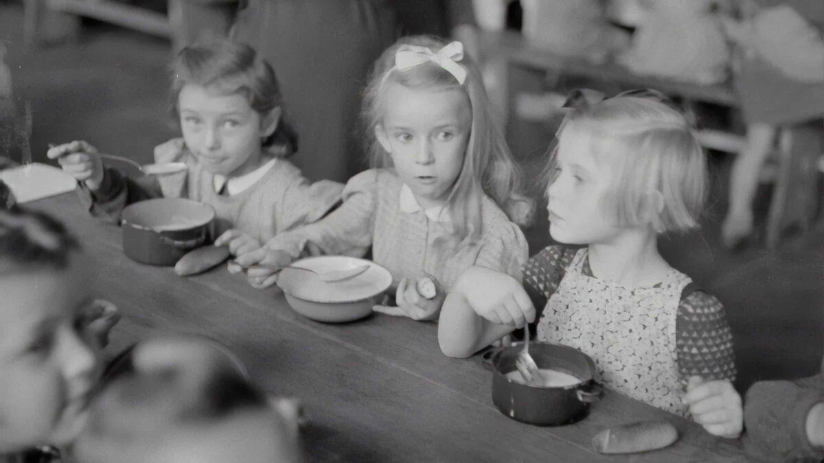 Foto van vroeger met 3 meisjes die pap eten uit een kommetje