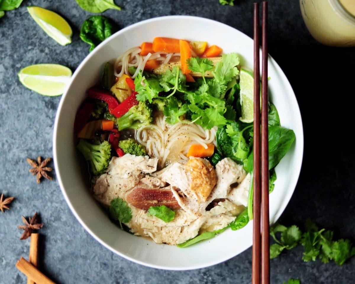 Gerecht met noodles groente en kip in een kom met stokjes erbij - foodtrends