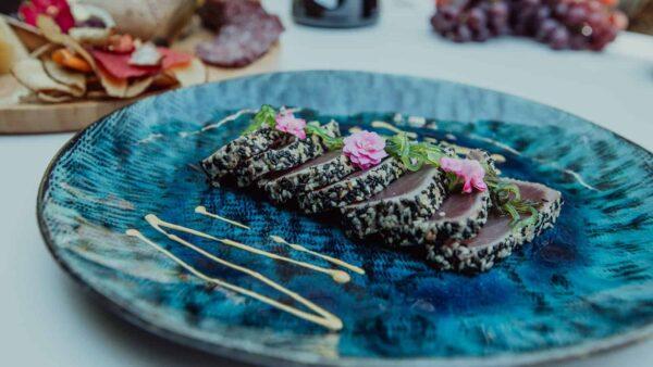 Gerecht met tonijn en bloemen op een blauw bord
