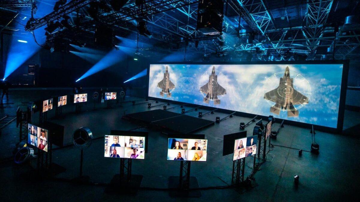 Groot scherm met 3 straaljagers en kleine schermen eromheen met beelden van de bezoekers van het online event (Photo @Floris Heuer)
