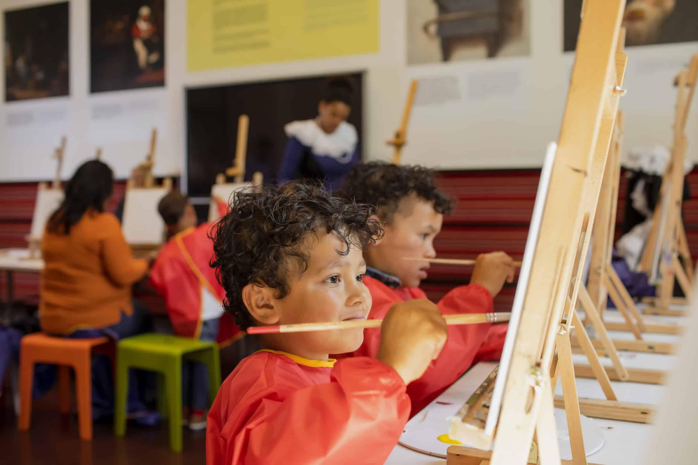 Kinderen met rode schorten die aan het schilderen zijn bij het Mauritshuis Den Haag