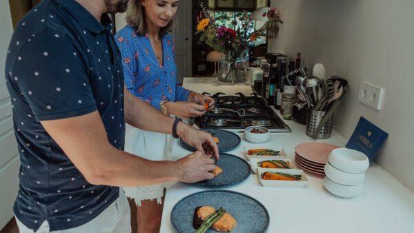 Man en vrouw die in een keuken gerechten met zalm maken van Caterbox
