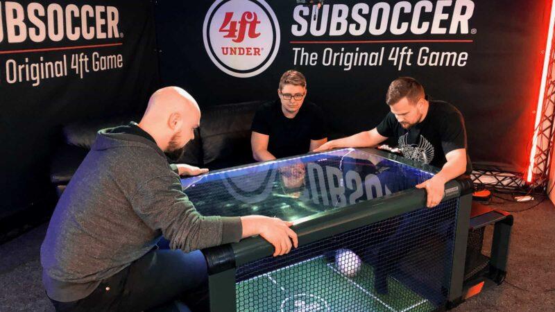 Subsoccer wedstrijd met twee mensen die onder een tafel doeltjes hebben en proberen te scoren