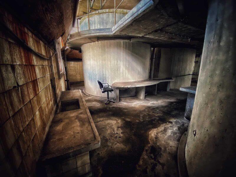 Verlaten febriek met bureaustoel aan een betonnen tafel