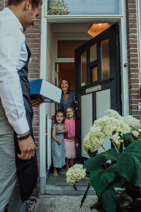 Vrouw met twee kinderen die de deur open doen als er een pakket wordt bezorgd