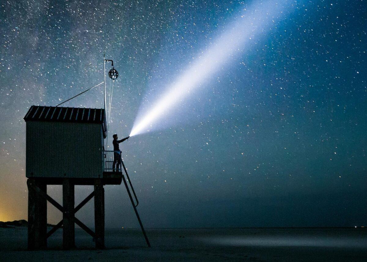Man die met zaklamp in een donkere zee schijnt vanaf een strandwachthuisje onder een sterrenhemel in Friesland - Photo Hans Jellema en Holland Boven Amsterdam