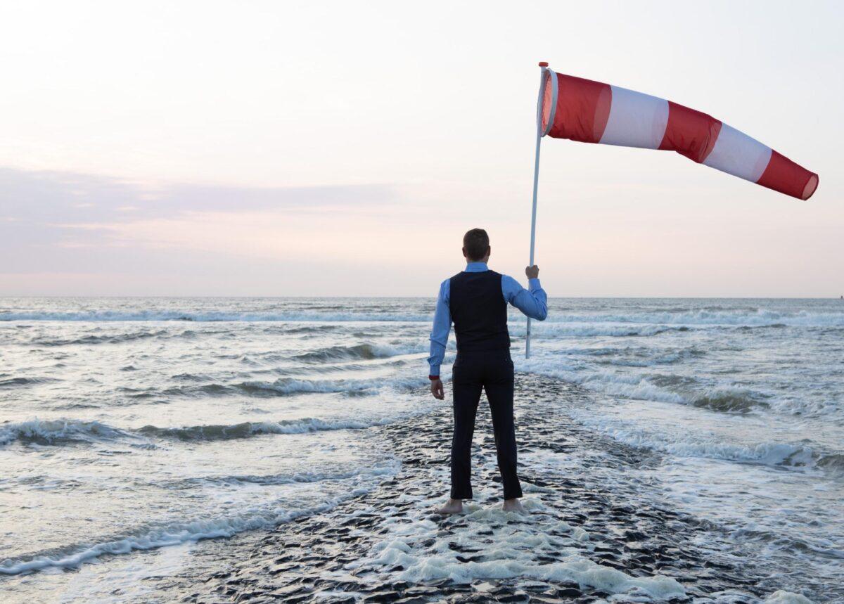 Man met windvlag met voeten in de zee