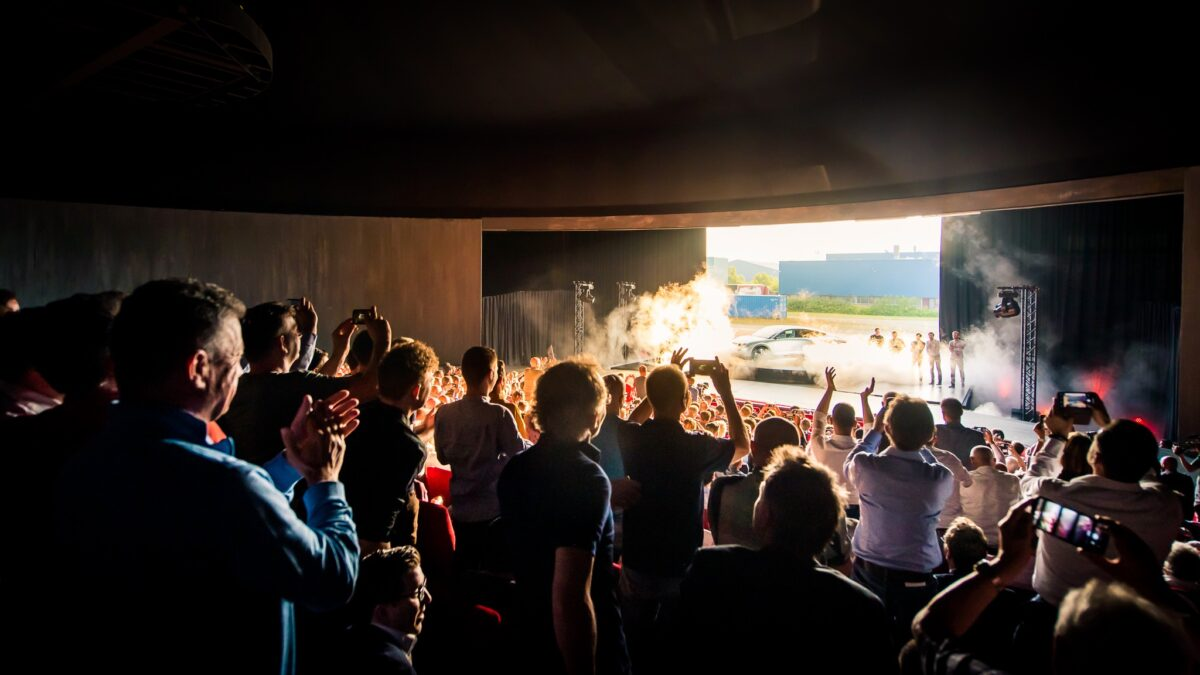 Plugged Live Shows optreden in zaal met auto op het podium en veel mensen