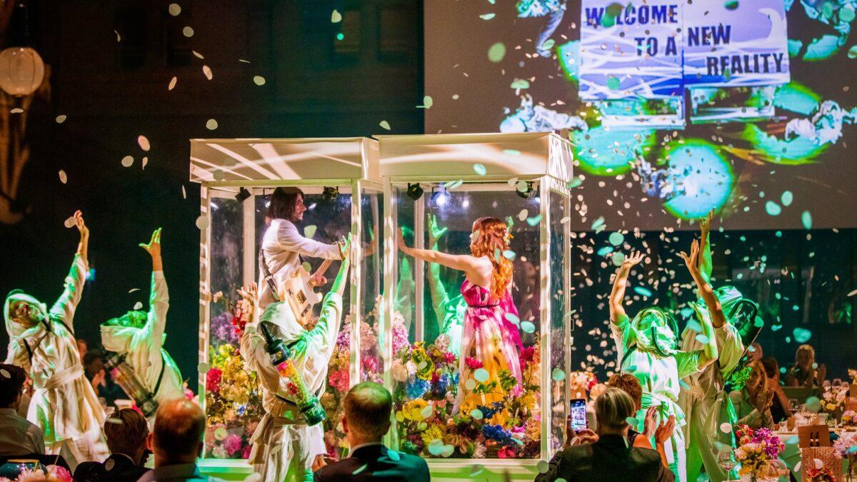 Plugged Live Events mensen in doorzichtige kooien met bloemen en dansers eromheen
