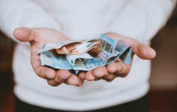 Twee handen met briefjes geld