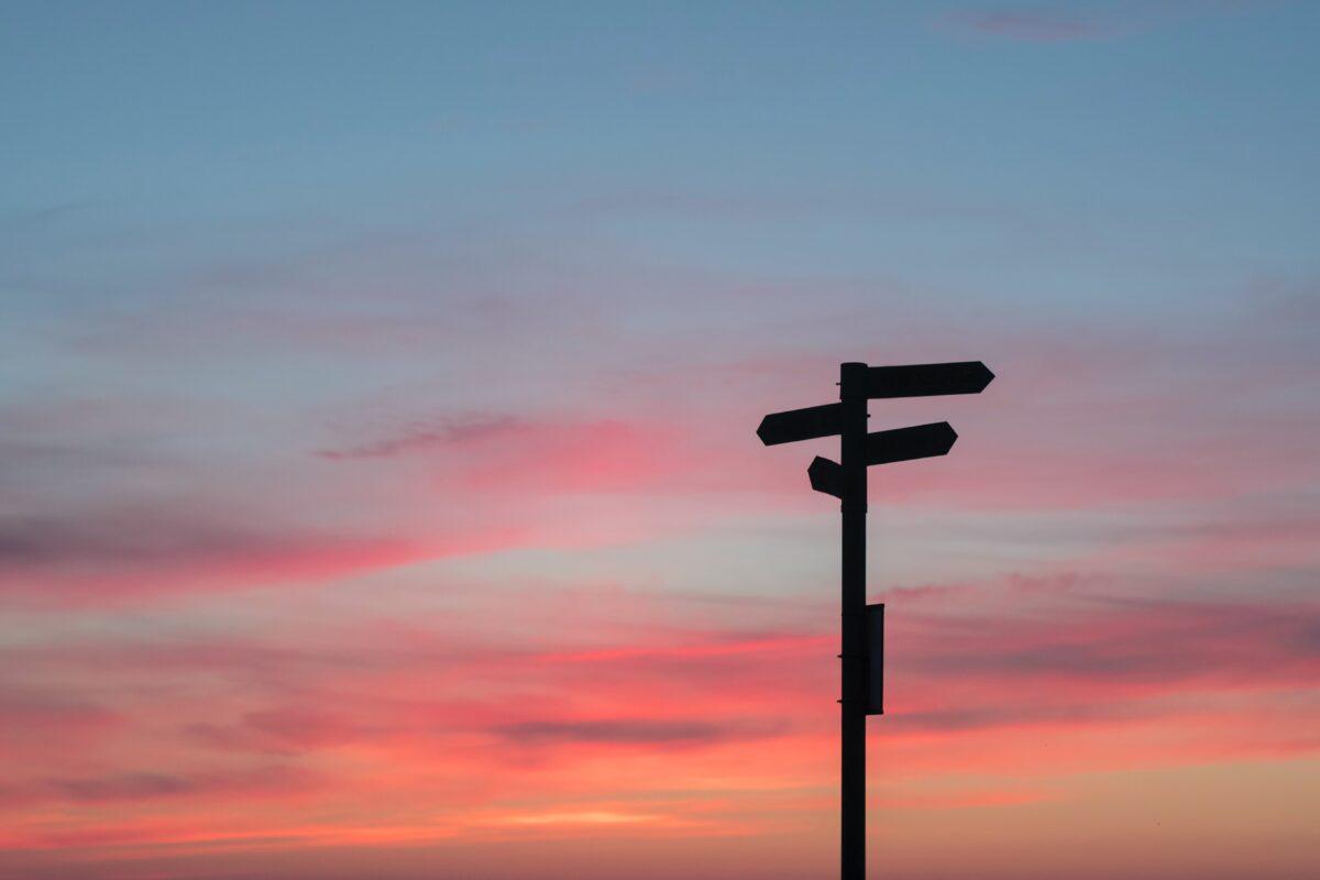 Wegwijzer in de schemering met een gekleurde lucht (Photo javier-allegue-barros)
