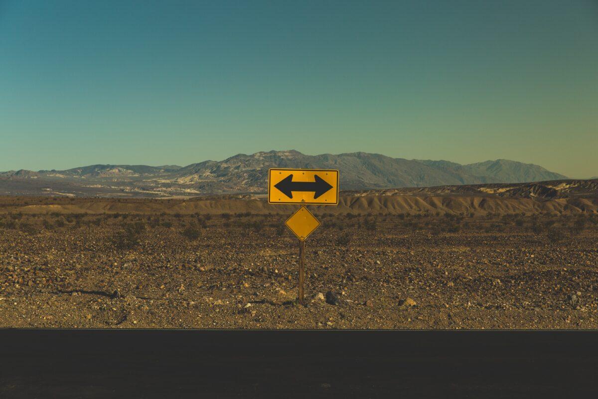 Woestijn met een bord met twee pijlen naar rechts en links (Photo pablo-garcia-saldana)