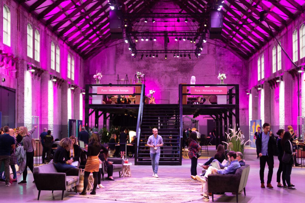 Booking.com event met spreker in een roze uitgelichte zaal