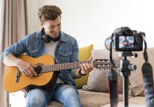 24streamer artiest met gitaar die wordt gefilmd