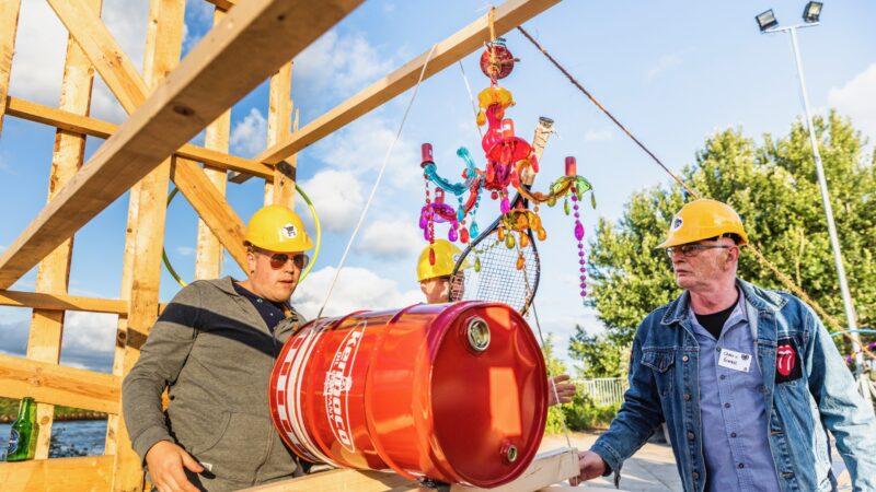 Chainreaction 3 mannen met gele helmen die een constructie bouwen