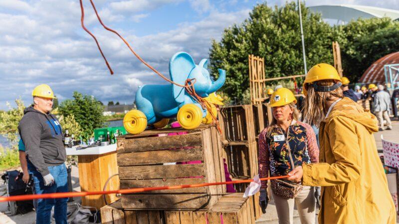 Chainreaction twee vrouwen en een man die een kettingreactie maken met een blauw olifantje