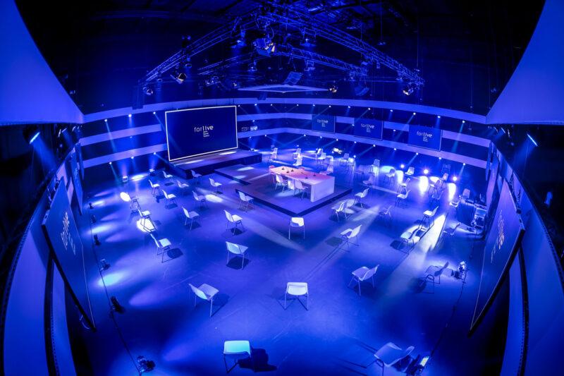 Zaal blauw uitgelicht met podium bij Central Studios voor hybride events