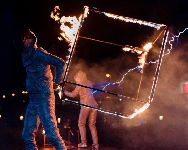 Kubus die in brand staat en een man houdt deze vast tijdens Tesla event