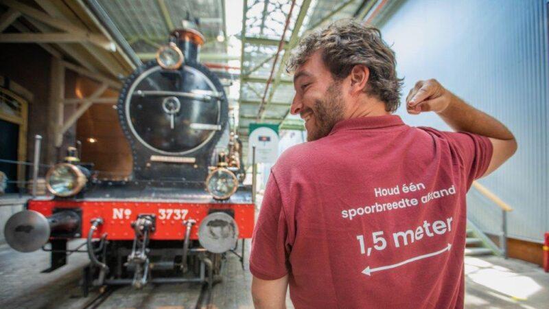 Medewerker Spoorwegmuseum bij trein en met shirt 1,5meter afstand houden