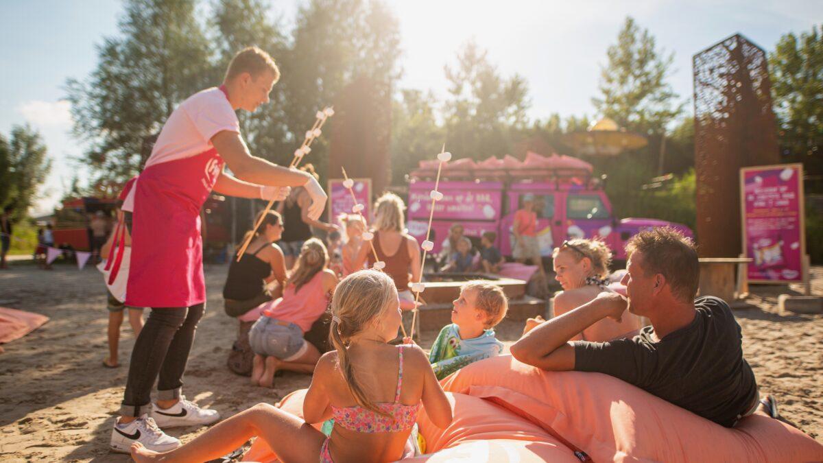 Mensen en kinderen op zitzakken die stokken met marshmellows krijgen (Foto- Marco Scheurink)
